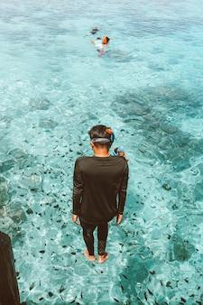 Ein mann im neoprenanzug springt im stehen mit vielen seefischen ins transparente meer
