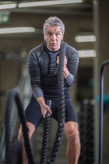 Ein mann im reifen alter konzentriert sich auf die richtige ausführung von seilübungen in einem fitnessstudio.