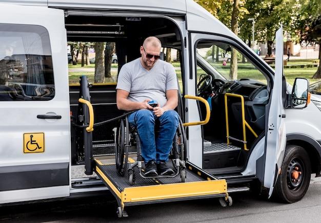 Ein mann im rollstuhl auf einem aufzug eines fahrzeugs für menschen mit behinderungen