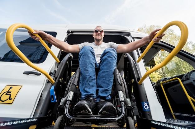 Ein mann im rollstuhl auf einem aufzug eines fahrzeugs für menschen mit behinderungen.