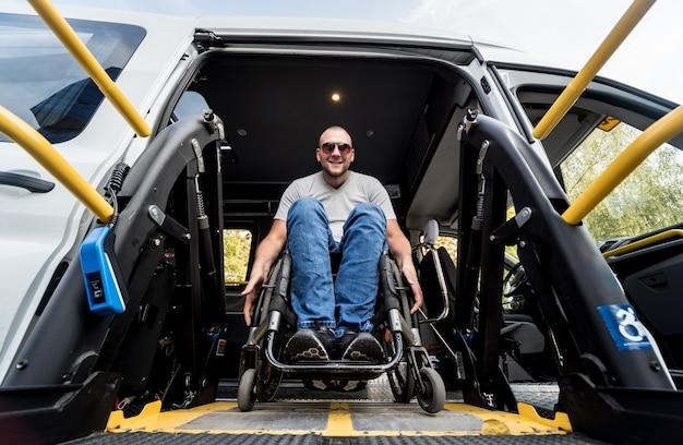 Ein mann im rollstuhl auf einem aufzug eines spezialfahrzeugs für menschen mit behinderungen.