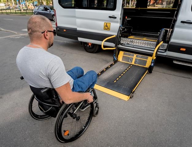 Ein mann im rollstuhl fährt zum aufzug eines spezialfahrzeugs für menschen mit behinderungen.