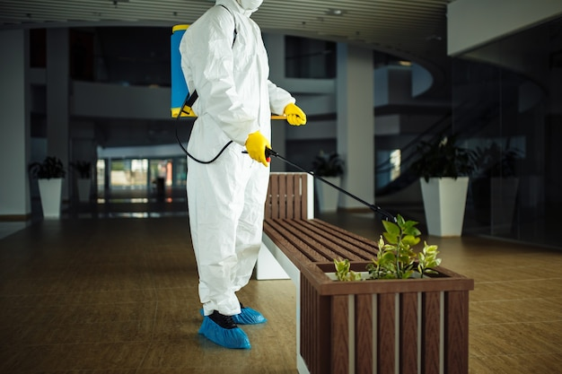 Ein mann im schutzanzug desinfiziert eine bank in einem leeren einkaufszentrum mit desinfektionsspray. aufräumen des öffentlichen platzes, um eine kovide ausbreitung zu verhindern.