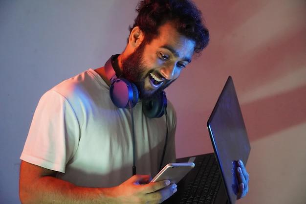 Ein mann im studio mit blauem und rotem licht mit laptop und handy