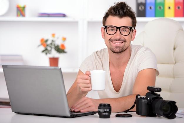 Ein mann im weißen hemd betrachtet foto in der kamera.