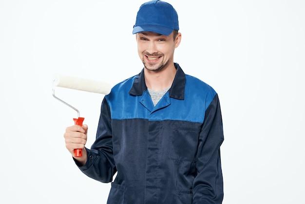 Ein mann in arbeitsuniform malt die wände und repariert das haus