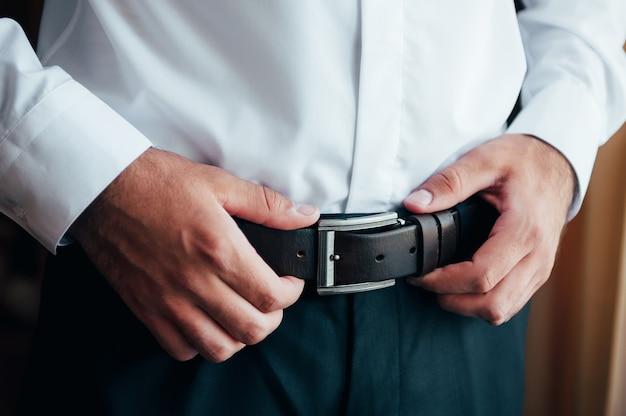 Ein mann in blauen hosen und einem weißen hemd knöpfte einen braunen lederhosengürtel zu