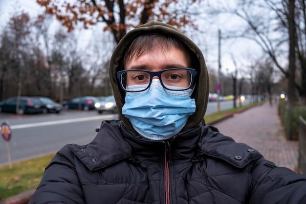 Ein mann in brille, medizinischer maske, kapuze und jacke bei bewölktem wetter, blick in die kamera, straße auf dem hintergrund