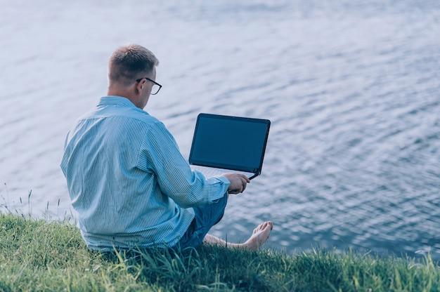 Ein mann in brille und hemd, der an der frischen luft an einem laptop arbeitet, gegen den raum eines flusses.