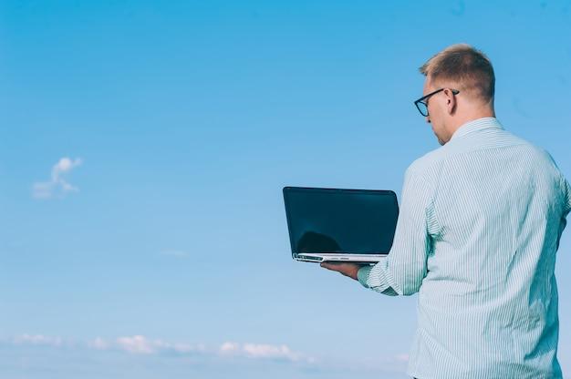 Ein mann in brille und hemd, der an der frischen luft an einem laptop arbeitet, gegen den raum eines himmels.