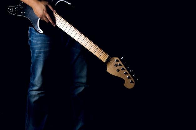 Ein mann in den jeans, die seine e-gitarre auf schwarzem hintergrund halten