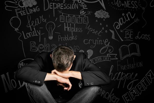 Ein mann in depression schließt mit seiner hand über eine gezeichnete tafel mit problemen