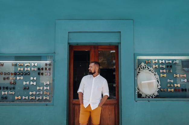 Ein mann in der altstadt von la laguna auf der insel teneriffa an einem sonnigen tag vor dem hintergrund einer theke mit schmetterlingen auf kostümen. schmetterlinge für herrenkostüme auf den kanarischen inseln. spanien.