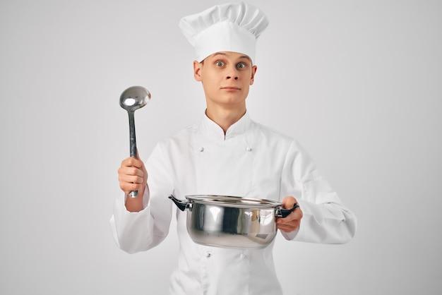 Ein mann in der uniform eines kochs mit einer pfanne in der hand, der professionelle restaurants kocht. foto in hoher qualität