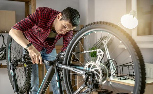 Ein mann in der werkstatt zerlegt sein fahrrad und repariert es. konzept der wartung und vorbereitung auf die neue saison