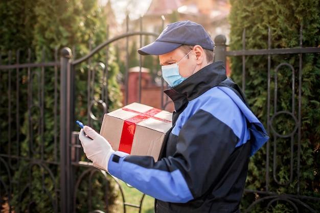Ein mann in dienstuniform, medizinischer maske und handschuhen liefert eine kiste an die haustür