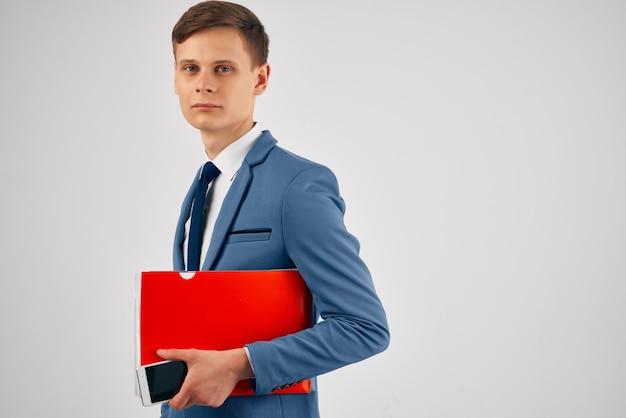 Ein mann in einem anzug mit einem roten ordner in der hand mit einer telefonkommunikation
