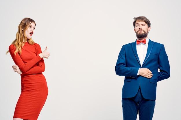 Ein mann in einem anzug neben einer frau in einem roten kleid kommunikationsmode isolierten hintergrund