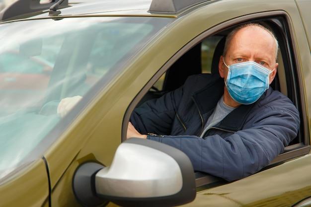 Ein mann in einem auto mit einer schutzmaske gegen die ausbreitung von coronavirus