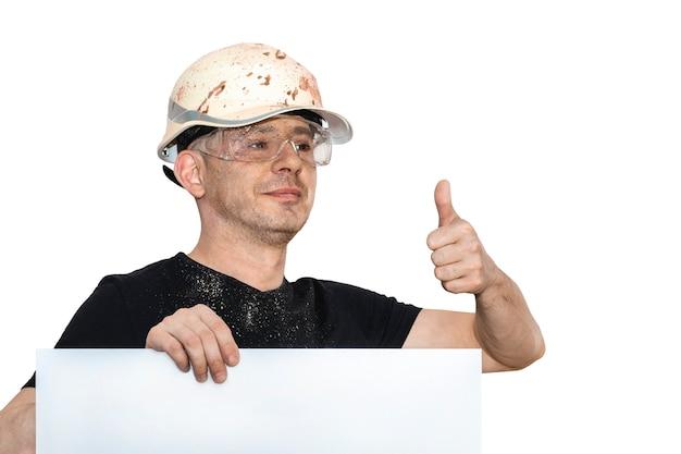 Ein mann in einem bauhelm zeigt einen daumen nach oben. alles ok. attrappe, lehrmodell, simulation. weißer isolierter hintergrund.