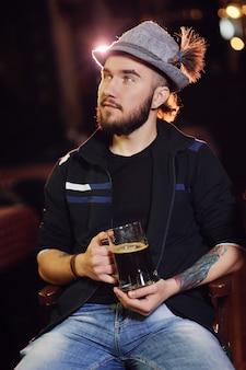 Ein mann in einem bayerischen hut, der bier in einer kneipe trinkt und fußball aufpasst