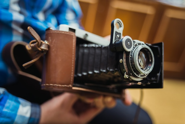 Ein mann in einem blauen hemd mit einer alten kamera
