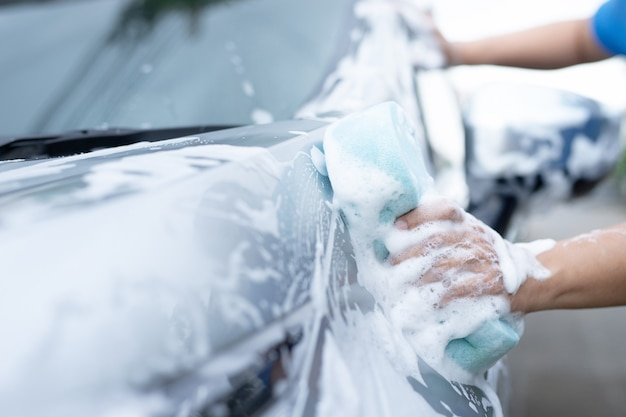 Ein mann in einem blauen hemd wäscht ein auto mit einem blauen schwamm.