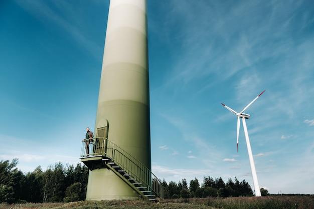 Ein mann in einem business-anzug mit einem grünen golfhemd steht neben einer windmühle