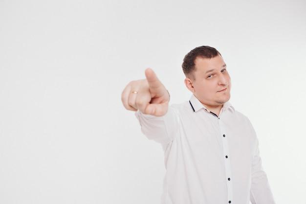Ein mann in einem business-anzug rennt und deutet auf eine weiße wand. gesten und mimik