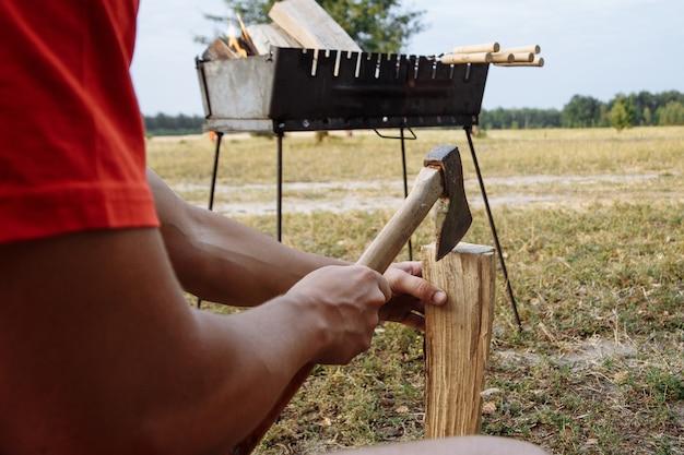 Ein mann in einem campingdorf hackt mit einer axt feuerholz zum grillen