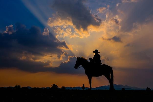 Ein mann in einem cowboy-outfit mit seinem pferd