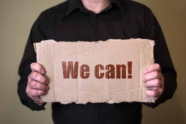 Ein mann in einem dunklen hemd, der ein stück pappe mit text hält, können wir.