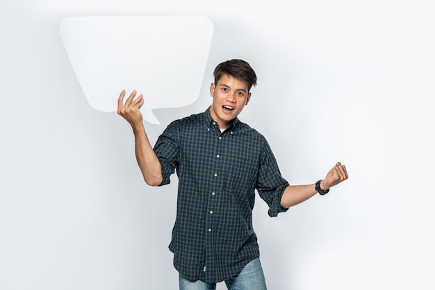 Ein mann in einem dunklen hemd hält ein gedankenkastensymbol