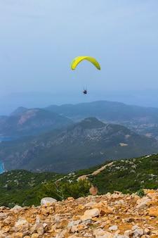 Ein mann in einem fallschirm fliegt über die berge