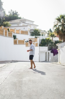 Ein mann in einem gestreiften hemd geht durch die straßen einer spanischen kleinstadt.