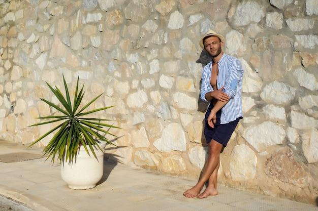 Ein mann in einem gestreiften hemd mit strohhut geht durch die straßen einer spanischen kleinstadt.