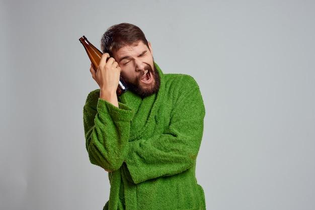 Ein mann in einem hausmantel morgens zu hause mit einer flasche bieralkohol ist gelangweilt und arbeitslos Premium Fotos