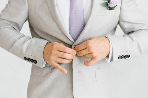Ein mann in einem hellgrauen anzug mit lila krawatte knöpft ihn zu.