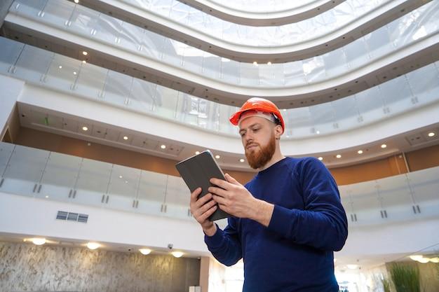 Ein mann in einem helm in einem großen raum mit einer tablette