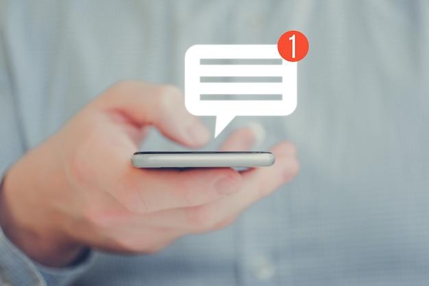 Ein mann in einem hemd hält ein telefon mit der hand. symbol für abstrakte benachrichtigung. social-networking-konzept.