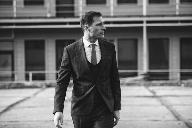 Ein mann in einem karierten anzug posiert auf der straße, um für männerkleidung zu werben.