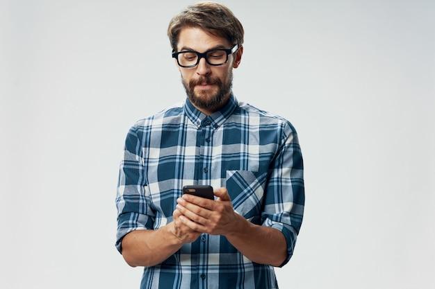 Ein mann in einem karierten hemd und einer brille mit einem mobiltelefon in der hand geschäftsfinanzmodell
