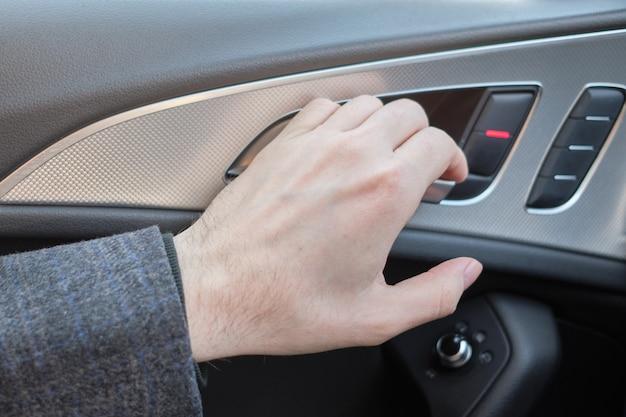 Ein mann in einem modernen auto. hand zieht den hebel, um die tür zu öffnen.