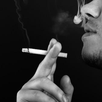 Ein mann in einem rauch, der eine monochrome zigarette raucht.