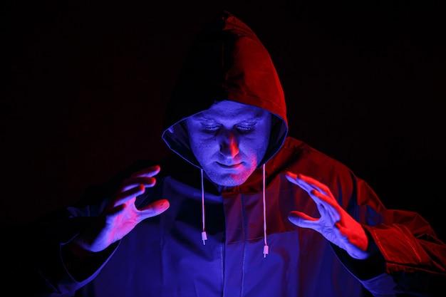 Ein mann in einem schutzanzug in einem dunklen raum. halloween-bildkonzept. virus schutz. beleuchtet mit farbigen lichtern