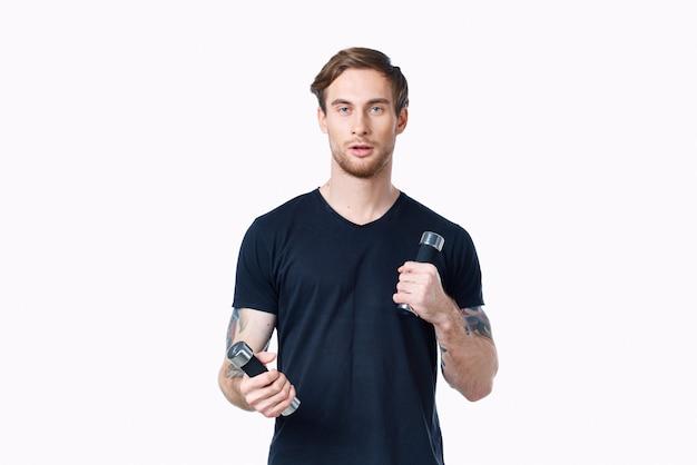 Ein mann in einem schwarzen t-shirt mit hanteln in den händen