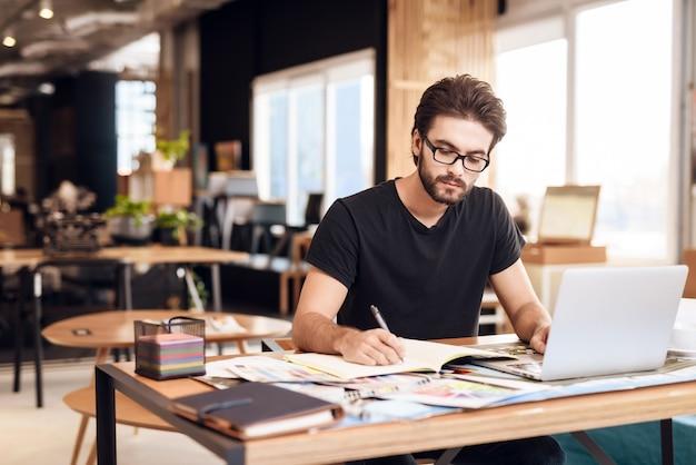 Ein mann in einem schwarzen t-shirt sitzt an einem tisch und arbeitet.