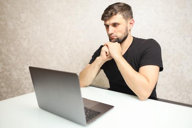 Ein mann in einem schwarzen t-shirt zeigt auf seinen laptop
