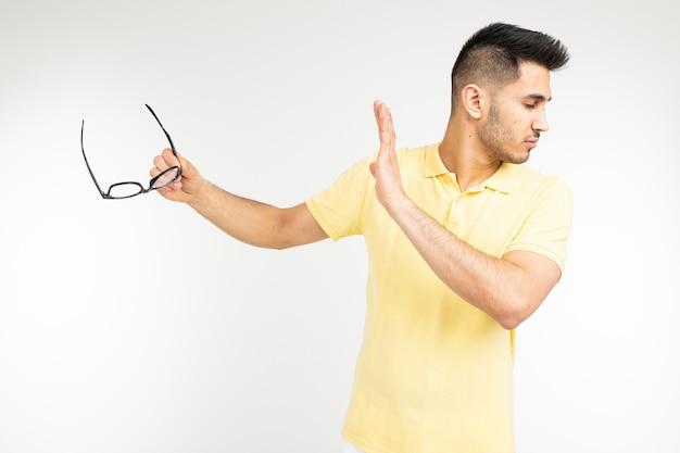Ein mann in einem t-shirt legt seine hand mit brille auf weißem hintergrund beiseite. neue vision