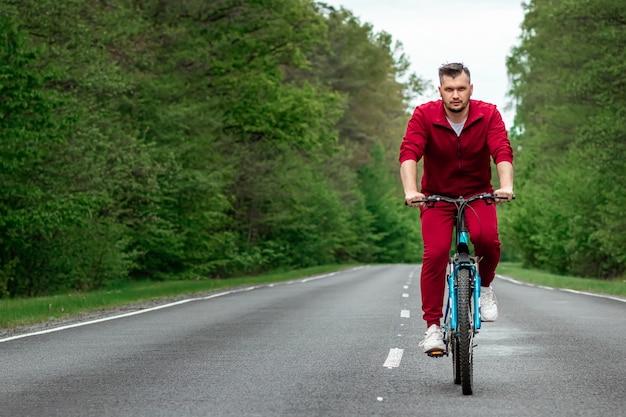 Ein mann in einem trainingsanzug auf einem fahrrad fährt auf einer straße im wald. das konzept eines gesunden lebensstils, cardio-training. copyspace.